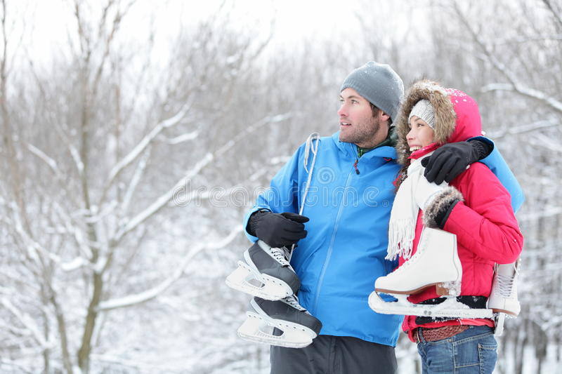 Young couple carrying ice skates. Young interracial couple in winter carrying ice skates standing close together looking out over a snowy winter landscape with royalty free stock image