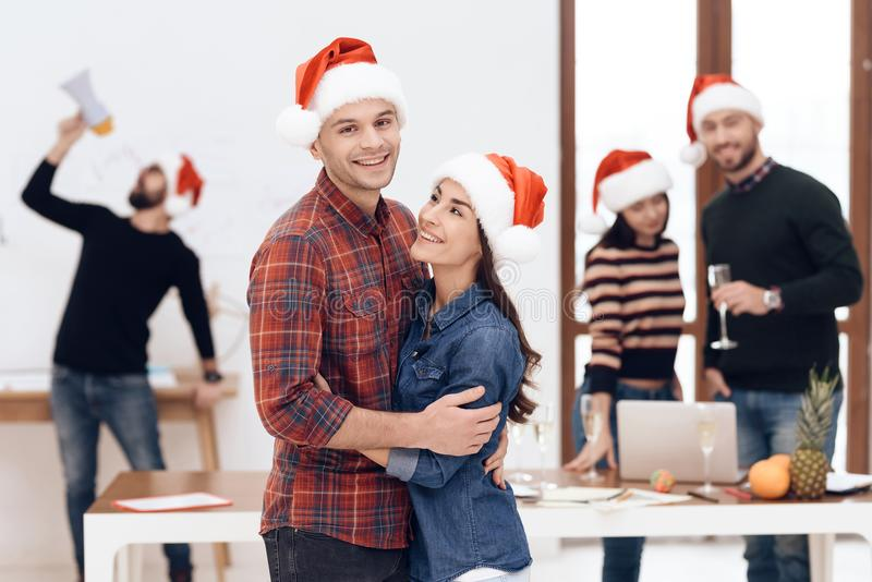 A young couple celebrates at a corporate celebration. They hold glasses with champagne in their hands. They have Santa Claus hats on their heads stock image