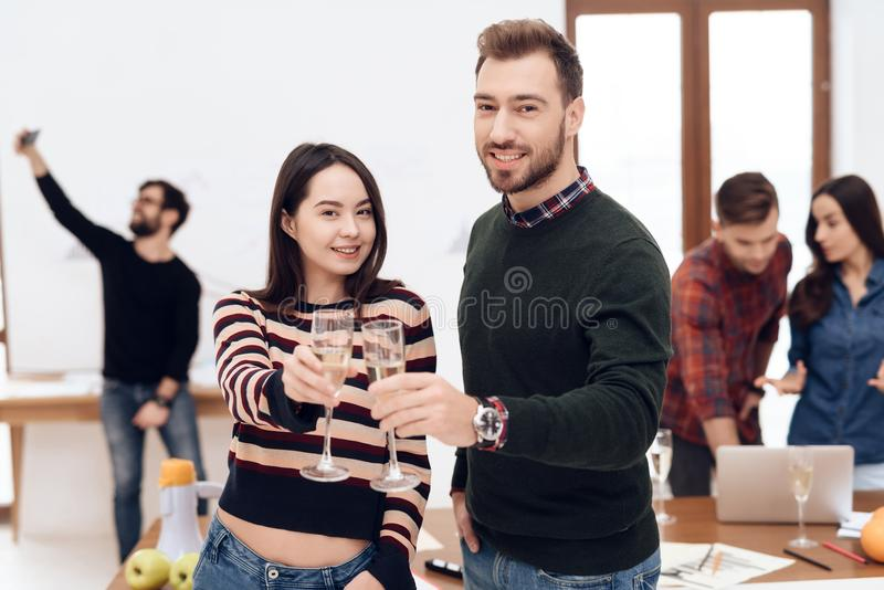 A young couple celebrates at a corporate celebration. They hold glasses with champagne in their hands royalty free stock photo