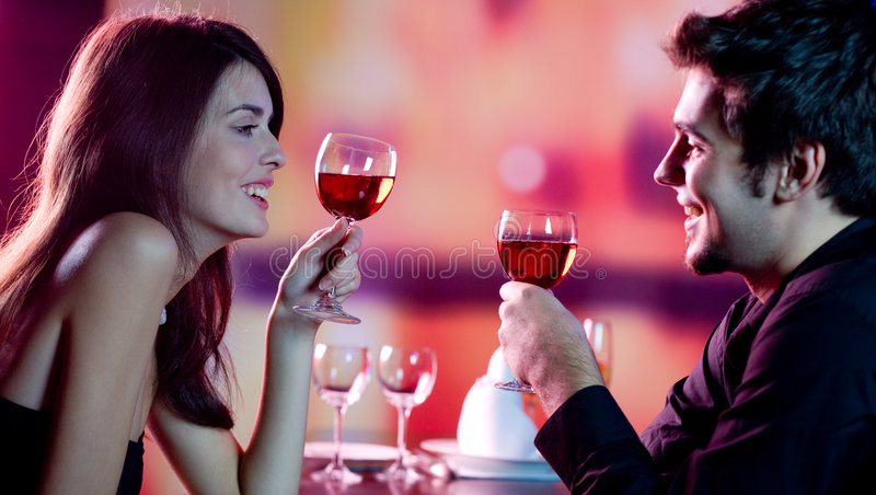 Young couple celebrating. Young happy amorous couple celebrating with red wine at restaurant