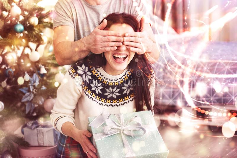 Young couple celebrating Christmas. A man suddenly presented a present to his wife. The concept of family happiness and royalty free stock image