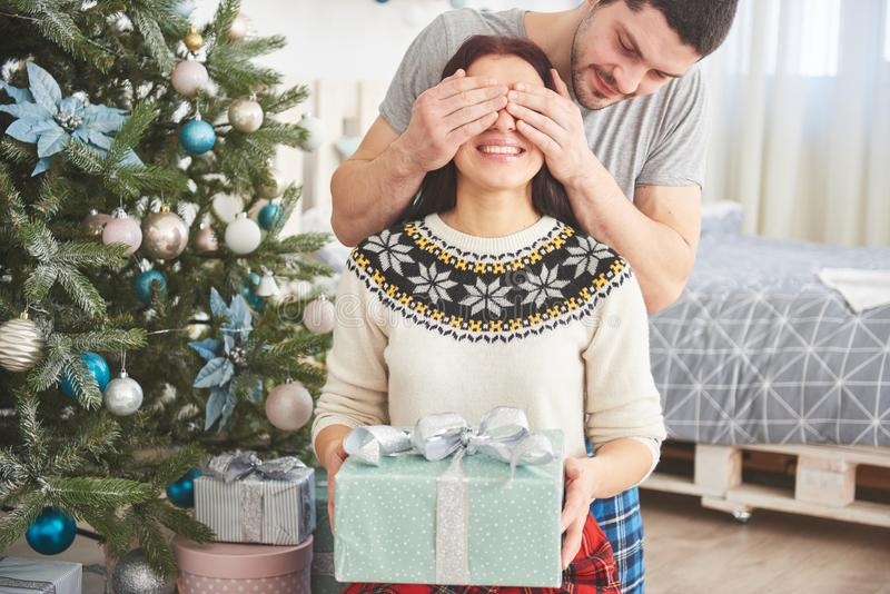 Young couple celebrating Christmas. A man suddenly presented a present to his wife. The concept of family happiness and well-being. Young couple celebrating royalty free stock photography