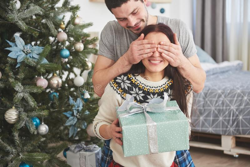 Young couple celebrating Christmas. A man suddenly presented a present to his wife. The concept of family happiness and well-being. Young couple celebrating stock photography