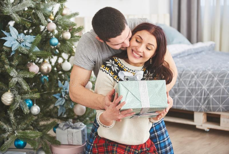 Young couple celebrating Christmas. A man suddenly presented a present to his wife. The concept of family happiness and well-being. Young couple celebrating royalty free stock image