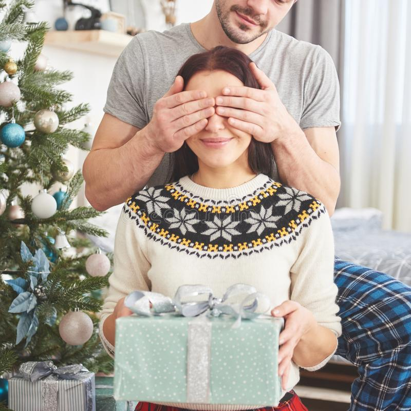Young couple celebrating Christmas. A man suddenly presented a present to his wife. The concept of family happiness and well-being. Young couple celebrating royalty free stock photo