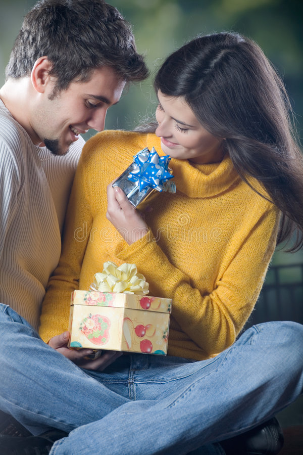 Young Couple Celebrating Event With Champagne Glasses And Gifts Royalty Free Stock Photography