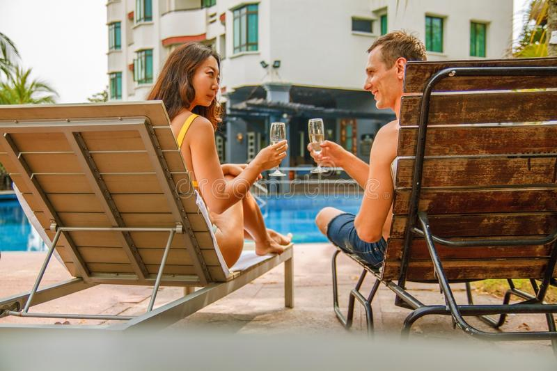 Young couple celebrating and lying on sunbeds, summer vacations and drinking champagne. royalty free stock image