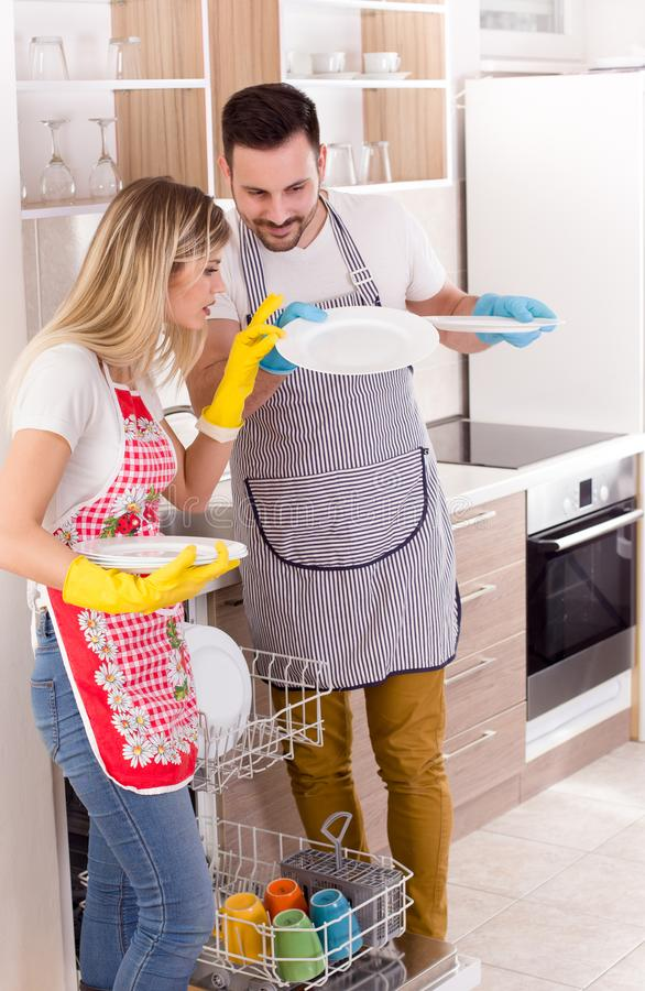 Couple with clean plates from dishwasher stock photography