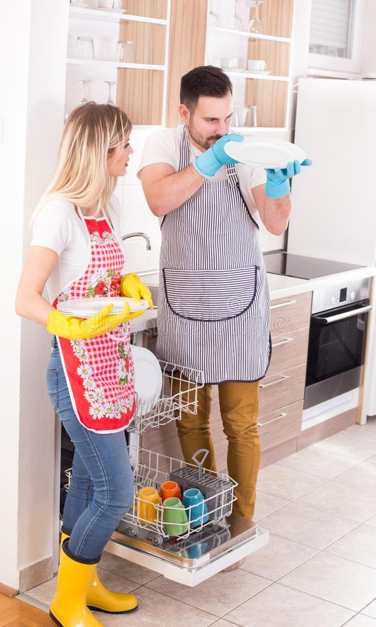 Couple with clean plates from dishwasher royalty free stock photo