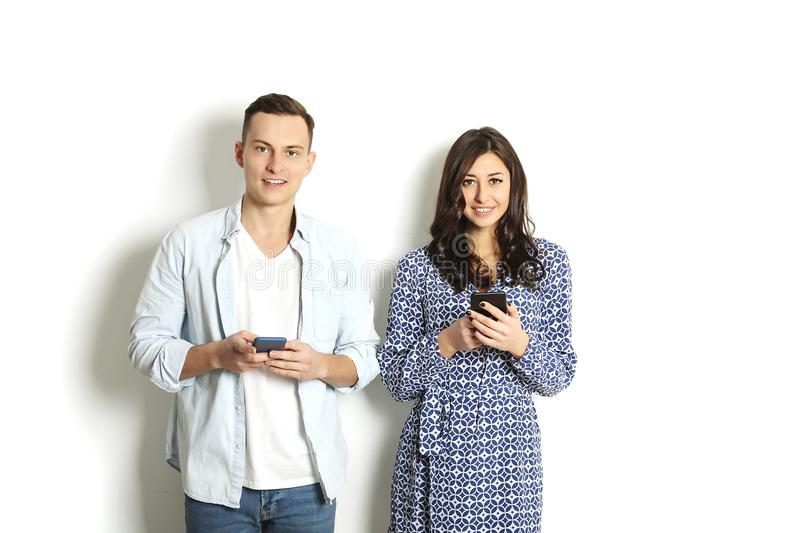 Young couple checking mobile phone, reading a message. Technology & relationship concept. Modern romance troubles. Male & female o royalty free stock photos