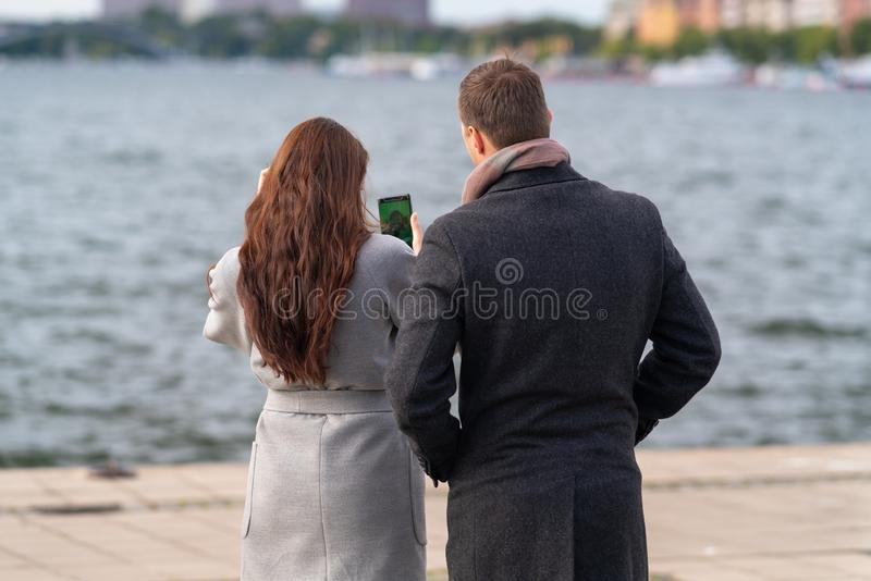 Young couple checking a photograph on their mobile royalty free stock photo