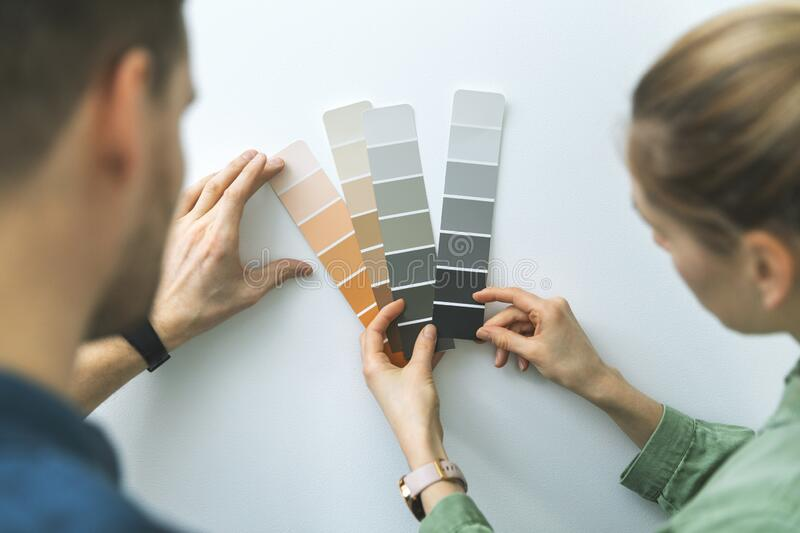 Young couple choosing paint color from samples for new home interior stock images