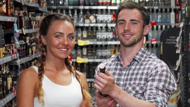 Young couple choosing wine to buy at the supermarket. Lovely couple examining wine bottle while shopping together at the supermarket. Beautiful women and her stock photos