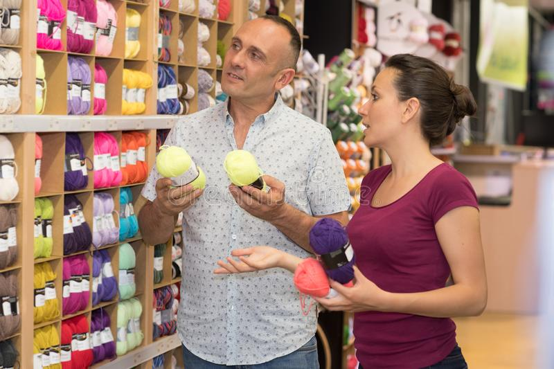 Young couple choosing wool at textile store. Couple royalty free stock photo