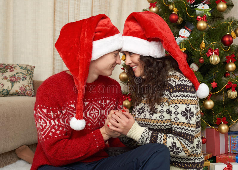 Young couple in christmas decoration. Home interior with gifts and fir tree. New year holiday concept. Love and tenderness. stock photos