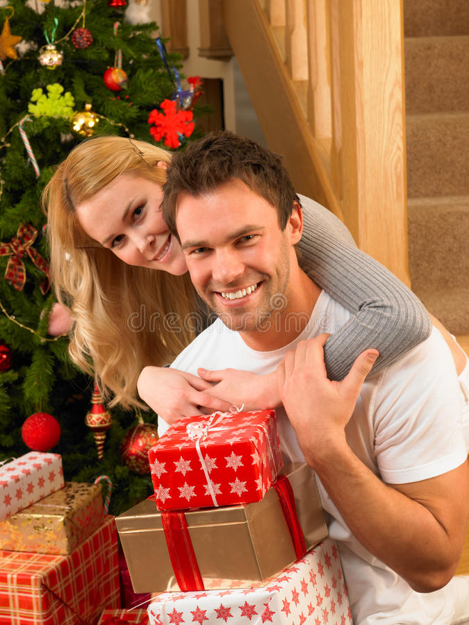 Young Couple at christmas exchanging gifts royalty free stock photography