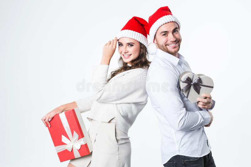 Young couple at Christmas in Santa Claus hats with gifts. stock photos