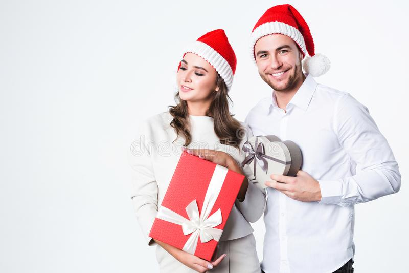 Young couple at Christmas in Santa Claus hats with gifts. royalty free stock photography