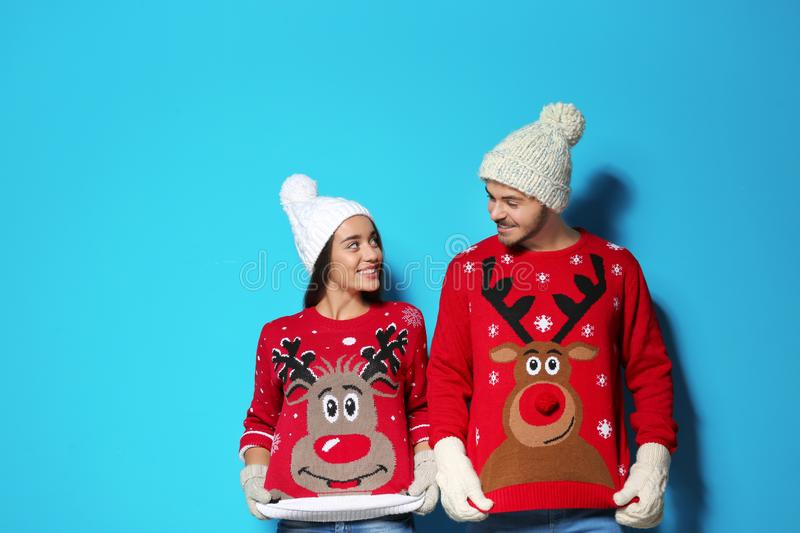 Young couple in Christmas sweaters and knitted hats. On color background stock photography