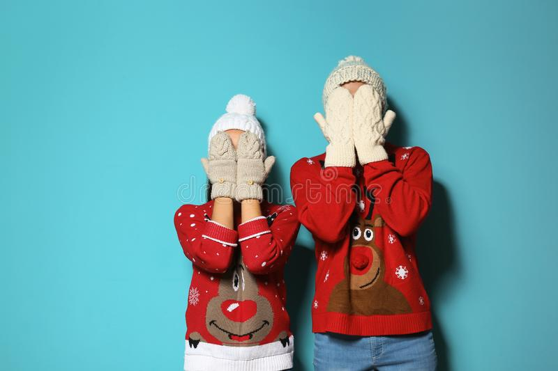 Young couple in Christmas sweaters and knitted hats. On color background royalty free stock photography