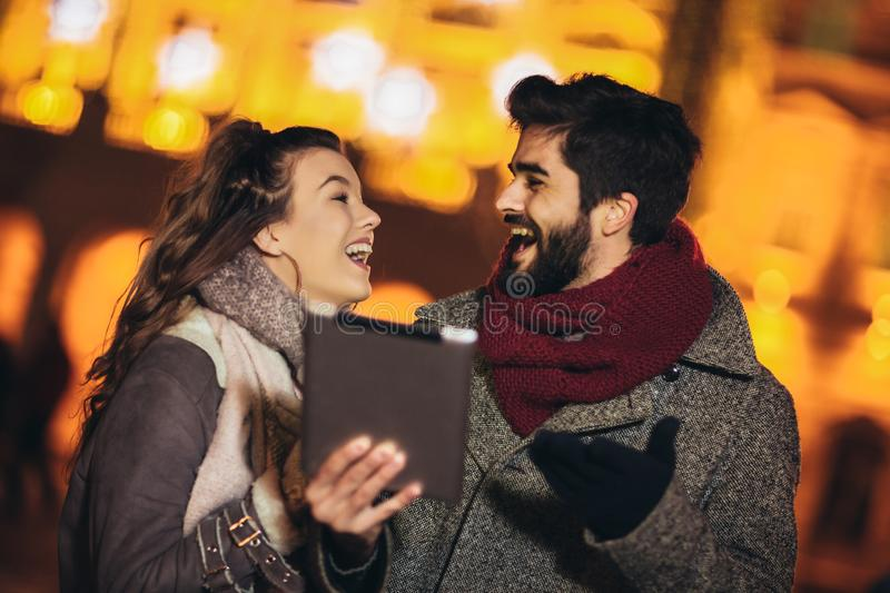 Couple in the city centre with holiday`s brights in background. Couple browsing digital tablet royalty free stock photo