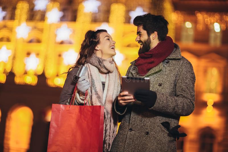 Couple in the city centre with holiday`s brights in background. Couple browsing digital tablet. They are using credit card stock image