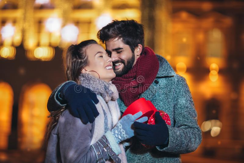Couple in the city centre with holiday`s brights in background. Man presenting gift to woman stock images