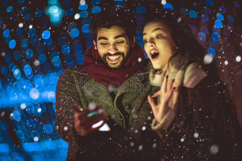 Couple in the city centre with holiday`s brights in background using phone stock photo