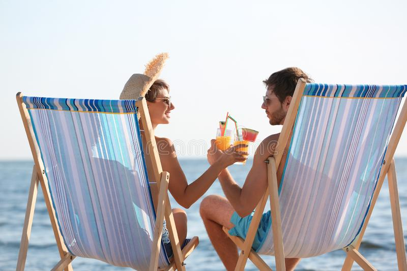Young couple with cocktails in beach chairs royalty free stock images