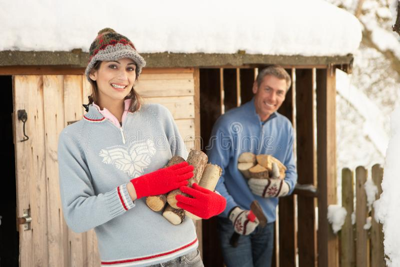 Young Couple Collecting Logs From Wooden Store stock photo