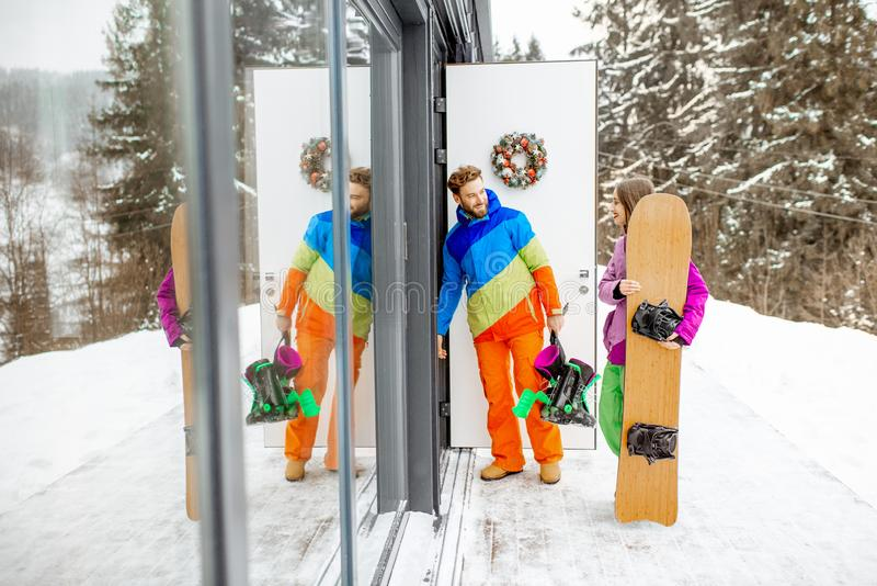 Couple in ski suits coming home in the mountains. Young couple in coloful ski suits entering home or hotel after snowboarding in the snowy mountains royalty free stock photography