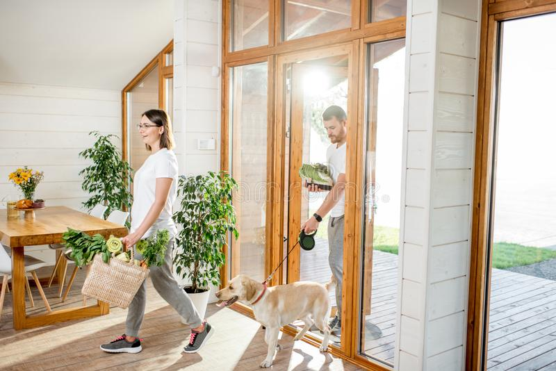 Couple coming home with dog and food. Young couple coming home with dog and fresh green vegetables from the garden or food market stock photos