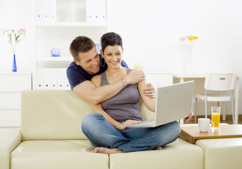 Young couple with computer. Happy young couple browsing internet on laptop computer at home, smiling stock photo