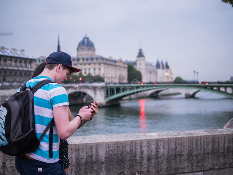 Young couple consult smart phone on a bridge over the Seine in P royalty free stock photo