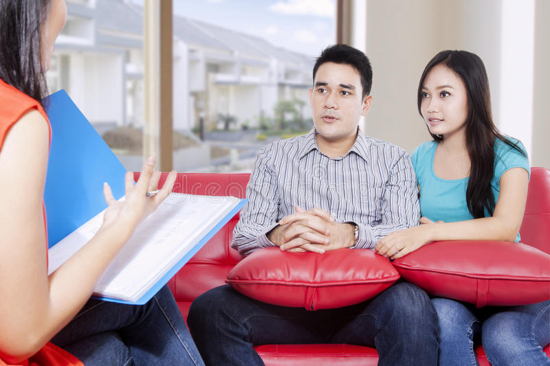 Young couple consulting by psychiatrist. Husband and wife are consulting of their problem by psychiatrist while sitting on the red couch in the house stock photos