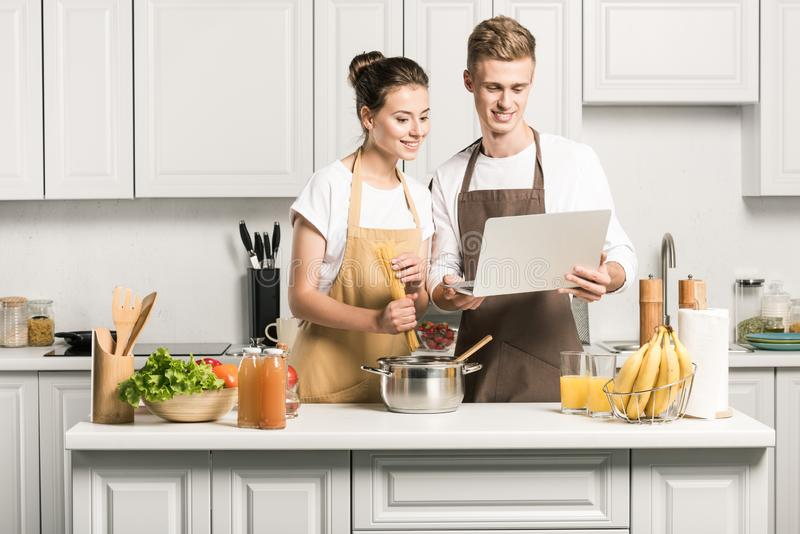 young couple cooking pasta and using laptop stock image