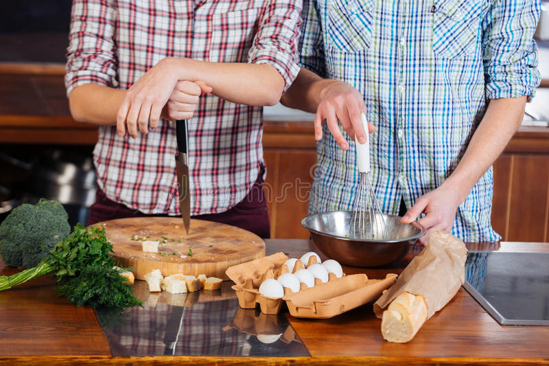 Young couple cooking together on the kitchen. Young couple in checkered shirts cooking together on the kitchen royalty free stock image