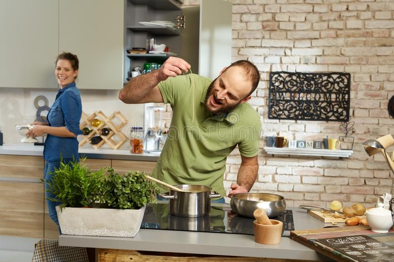 Young couple cooking together in kitchen royalty free stock photos