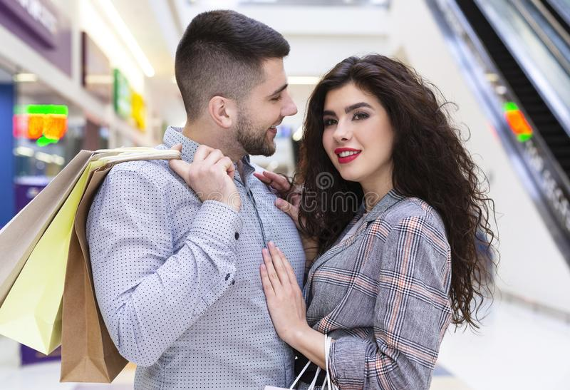Young couple cuddling in mall after shopping royalty free stock photo
