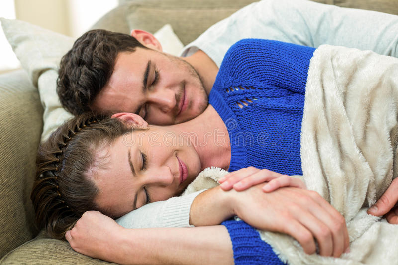 Young Couple Cuddling On The Sofa Stock Image - Image of