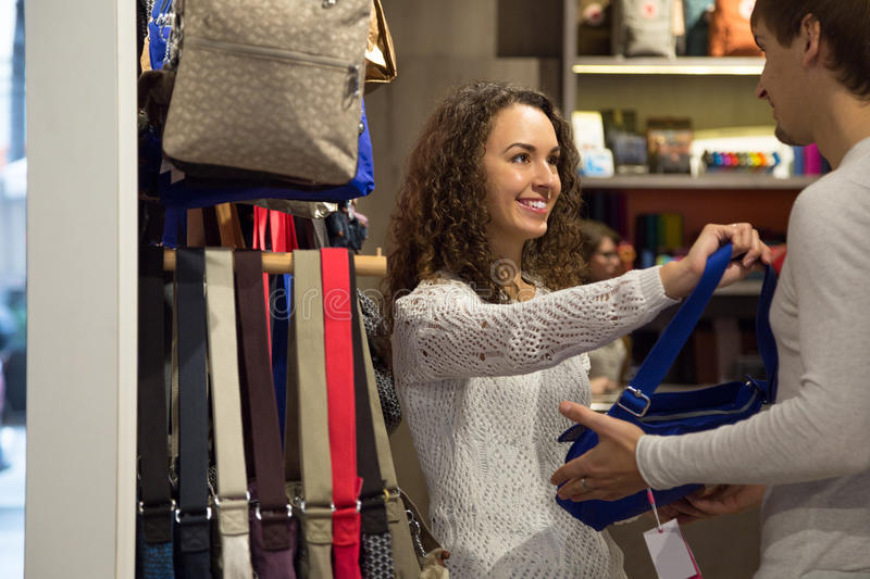 Young couple customers looking at female handbags royalty free stock image