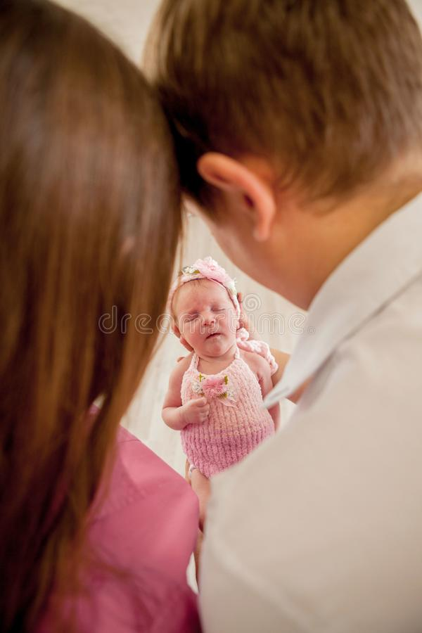 Young couple with cute little baby. Smiling mother and father holding their newborn baby daughter at home. couple kissing. hugging royalty free stock photo