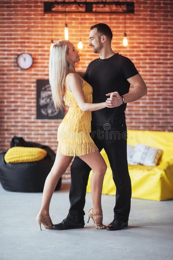Young couple dancing latin music: Bachata, merengue, salsa. Two elegance pose on cafe with brick walls stock images