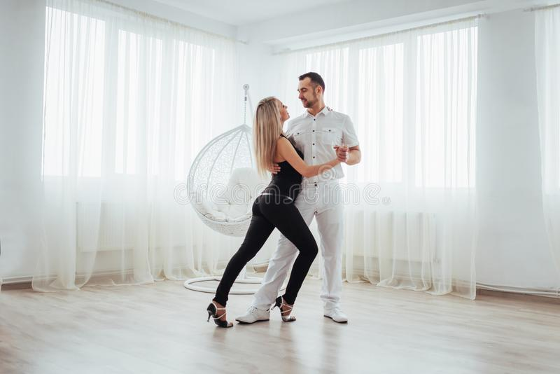 Young couple dancing latin music: Bachata, merengue, salsa. Two elegance pose on white room royalty free stock image