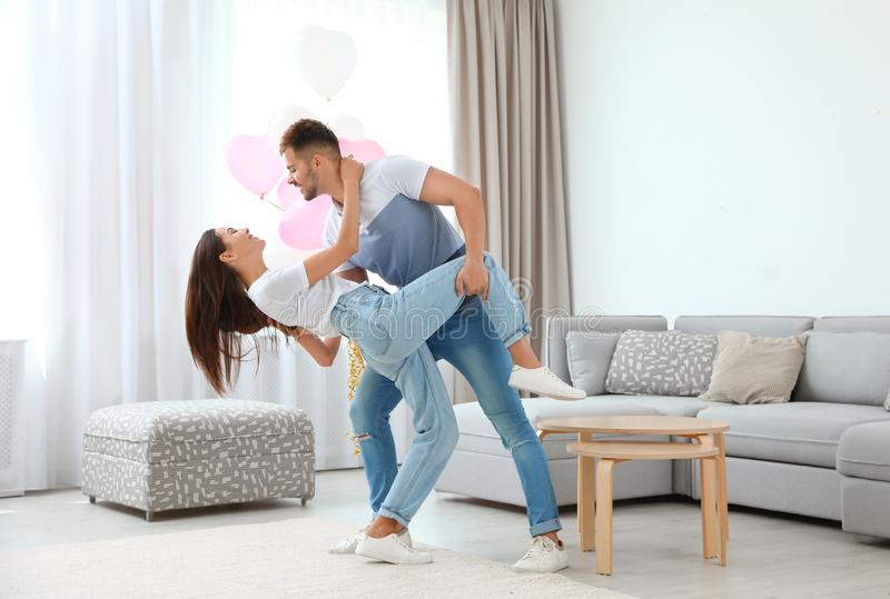 Young couple dancing in living room decorated with balloons. Celebration of Saint Valentine`s Day. Young couple dancing in living room decorated with air stock photos