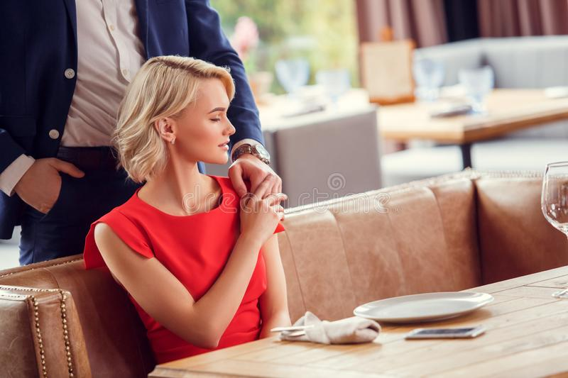 Young couple on date in restaurant man standing behind sitting woman holding his hand sensual royalty free stock photography