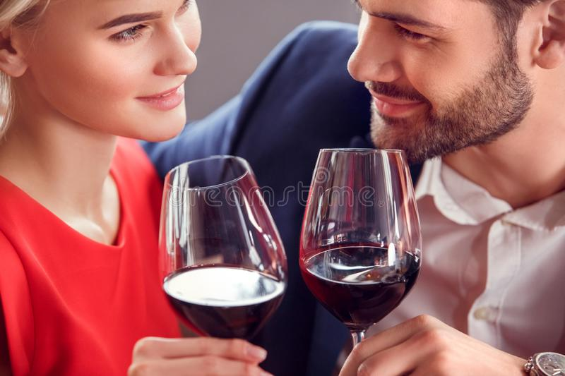 Young couple on date in restaurant sitting drinking wine looking at each other passionate royalty free stock image