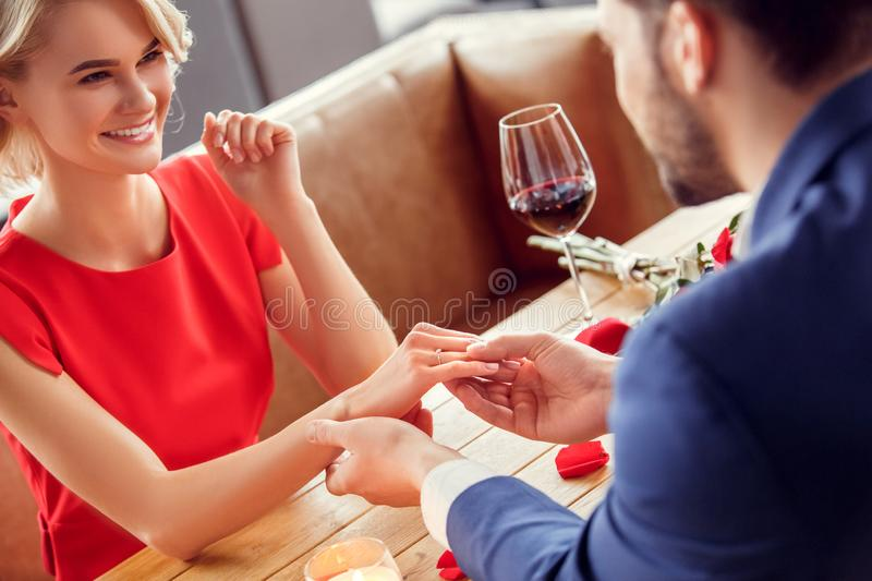 Young couple on date in restaurant sitting man holding hand of woman wearing proposal ring cheerful stock image