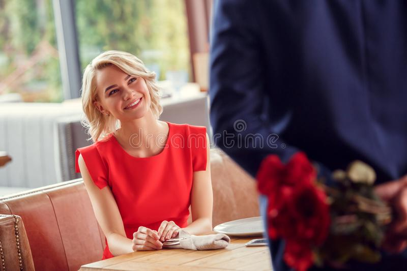 Young couple on date in restaurant woman sitting cheerful looking anticipating at man holding bouquet behind back close royalty free stock photo