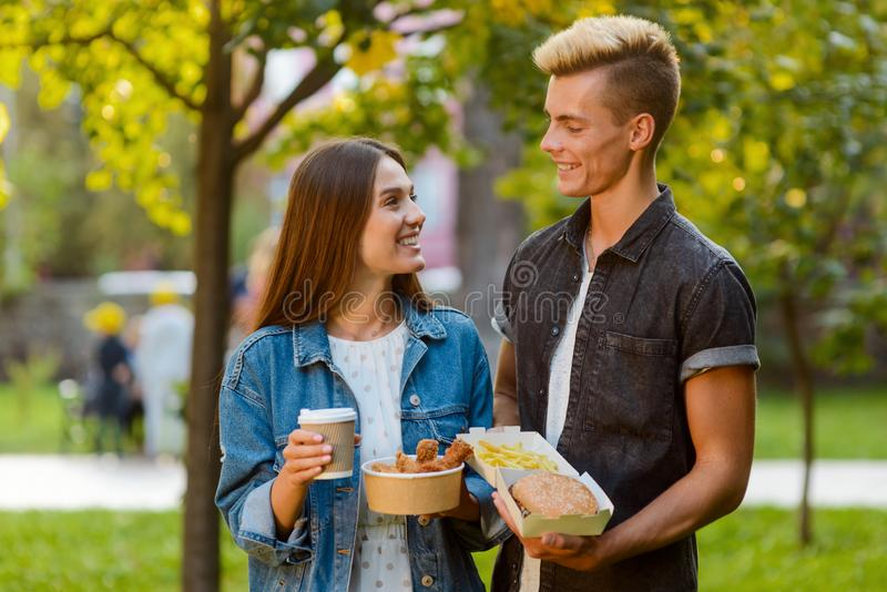 Young couple on a date. Beautiful girl and handsome guy eating fast food, drinking coffee and looking at each other. Love is royalty free stock image